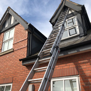 Painter and decorator using ladders outside semi-detatched house